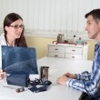 Doctor Explaining Lung X-ray Results to Middle Aged Patient in Consulting Room — Stock Photo #75286523