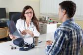Female Doctor and Middle Aged Patient Discussing Lung X-ray Results in Consulting Room — Foto Stock