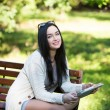 Girl student electronic tablet sitting on a bench in the park — Stock Photo #65137973