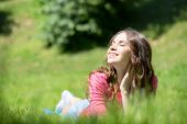 Woman lying in grass and smiling — Stock Photo