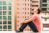 Man sitting on a Corbel — Stock Photo