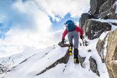 A climber ascending a snow covered ridge — Stock Photo