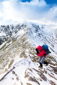 A climber ascending a snow covered ridge — Stock Photo