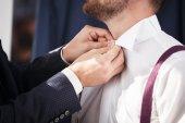 Groomsman helps to groom to put on shirt. — Stock Photo