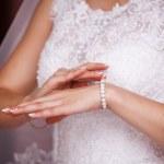 Bride puts on pearl bracelet. Focused on bracelet — Stock Photo #66419341