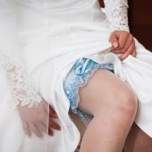 Bride puts on blue garter — Stock Photo