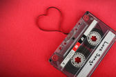 Vintage audio cassette with loose tape shaping a heart — Stock Photo