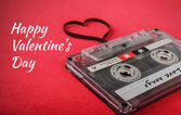 Vintage audio cassette with loose tape shaping a heart — Stockfoto