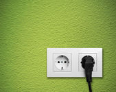 White electric outlet mounted on green wall — Stockfoto
