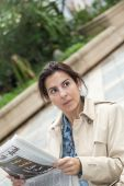 Brunette woman reading the newspaper — Stockfoto