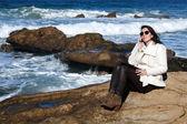 Attractive woman on seashore talking on the phone — Stock Photo