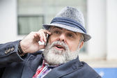 Attractive old man with beard and hat talking on phone — Stock Photo