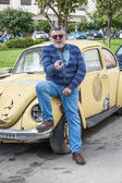 Man with an old classic yellow wolsvagen — Stock Photo