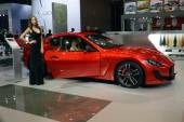 A young woman from the Maserati team. In the long black dress near car. Gran Turismo. Red Car. Moscow International Automobile Salon Luxury Premium — Stock fotografie