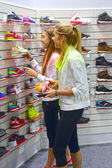 Young women in the department of sports shoes — Stock Photo