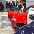 Постер, плакат: A young woman from the team Maserati near car Moscow International Automobile Salon Red and Dark Blue Maserati
