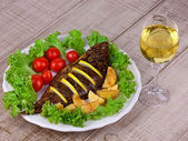 Whole grilled fish carp served with potatoes, tomatoes cherry and salad — Stock Photo