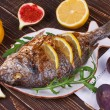 Whole grilled fish dorado served with lemon and figs — Stock Photo #57454961