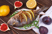 Whole grilled fish dorado served with lemon and figs — Stock Photo