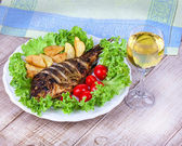 Whole grilled fish carp served with potatoes, tomatoes cherry, salad and lemon — Stock Photo
