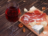 Glass of wine, cheese and on wooden background — Stock Photo