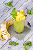 Fresh mango fruit juice in a glass and slices of mango. Close-up. Studio photography. — Stock Photo