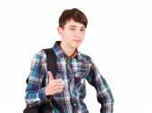 Ready to study. Handsome teenager carrying backpack on one shoulder and smiling isolated on white background — Stok fotoğraf