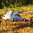 Homeless man is sleeping on a park bench — Stock Photo #68768423