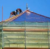 Roofers are working on the top of an old building — Fotografia Stock