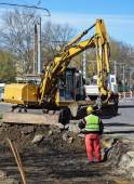 Excavator is working at the road construction — Stock Photo