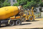 Cement mixer truck and an excavator at the construction site — Stock Photo
