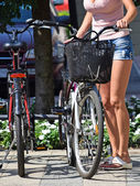 Woman with bicycle in the city — Stock Photo