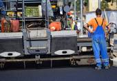 Road construction with an asphalt paving vehicle — Stock Photo
