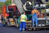 Asphalt paving vehicle at the road construction — Stock Photo