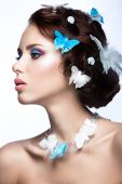 Beautiful girl with bright blue makeup and butterflies in her hair. — Stockfoto