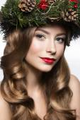 Beautiful girl with a wreath of fir branches and cones. New Year image. Beauty face. — Stock Photo
