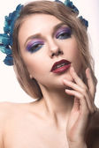 Beautiful blond girl with bright make-up and purple blue flowers in her hair. Beauty face. — Stock fotografie