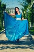Mooie vrouw blote voeten dansen in een lange blauwe jurk — Stockfoto