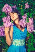 Beautiful woman enjoying the smell of flowers — Stock Photo