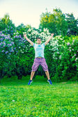 Young man jumping on summer field — Stock Photo