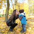 Mother with the son is among autumn foliage — Stock Photo #58151909