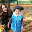 Mother with the son is among autumn foliage — Stock Photo #58151949