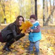 Mother with the son is among autumn foliage — Stock Photo #58151967