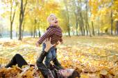 Mother and the kid walk in autumn park — Stock Photo