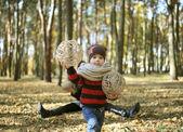 The charming kid plays among autumn gold foliage — Stock Photo