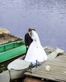 The groom and the bride kiss each other in the boat — Stock Photo
