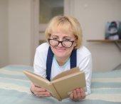 La mujer que llevaba gafas lee el libro — Foto de Stock