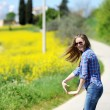 The girl goes on the road among yellow flowers — Stock Photo #73472253