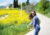 The girl goes on the road among yellow flowers — Stock Photo