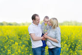 Family from three people on a rape field — Stock Photo